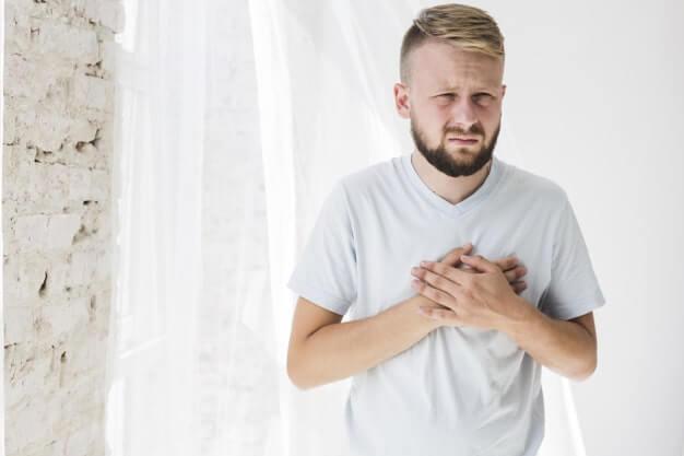 Homem branco de camisa branca apertando o coração com as duas mãos. Seu rosto aparenta estar preocupado.
